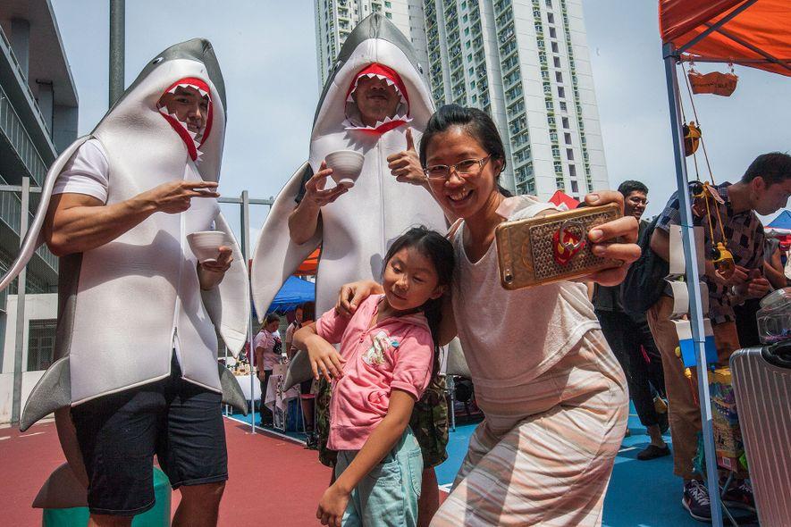 Une mère et sa fille posent lors d'un festival végétalien, où deux hommes déguisés en requins ...