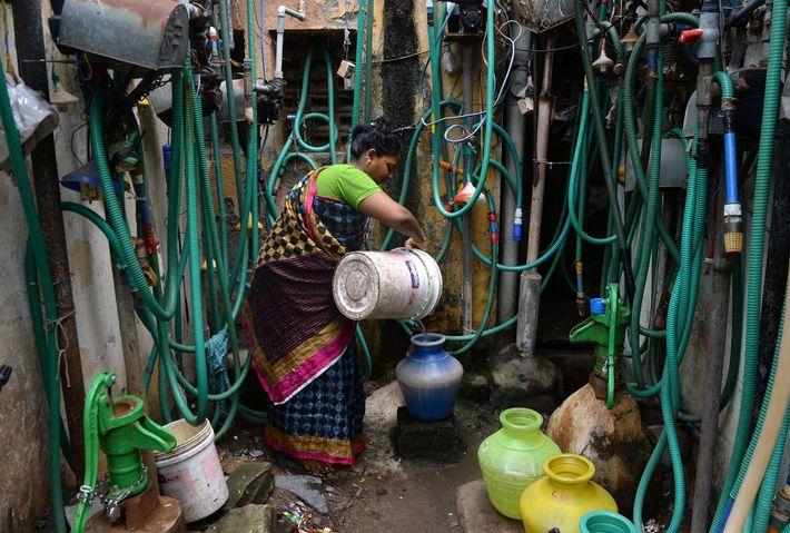 Une habitante de Chenai remplit une jarre d'eau au robinet le 26 juin 2019. L'approvisionnement en ...