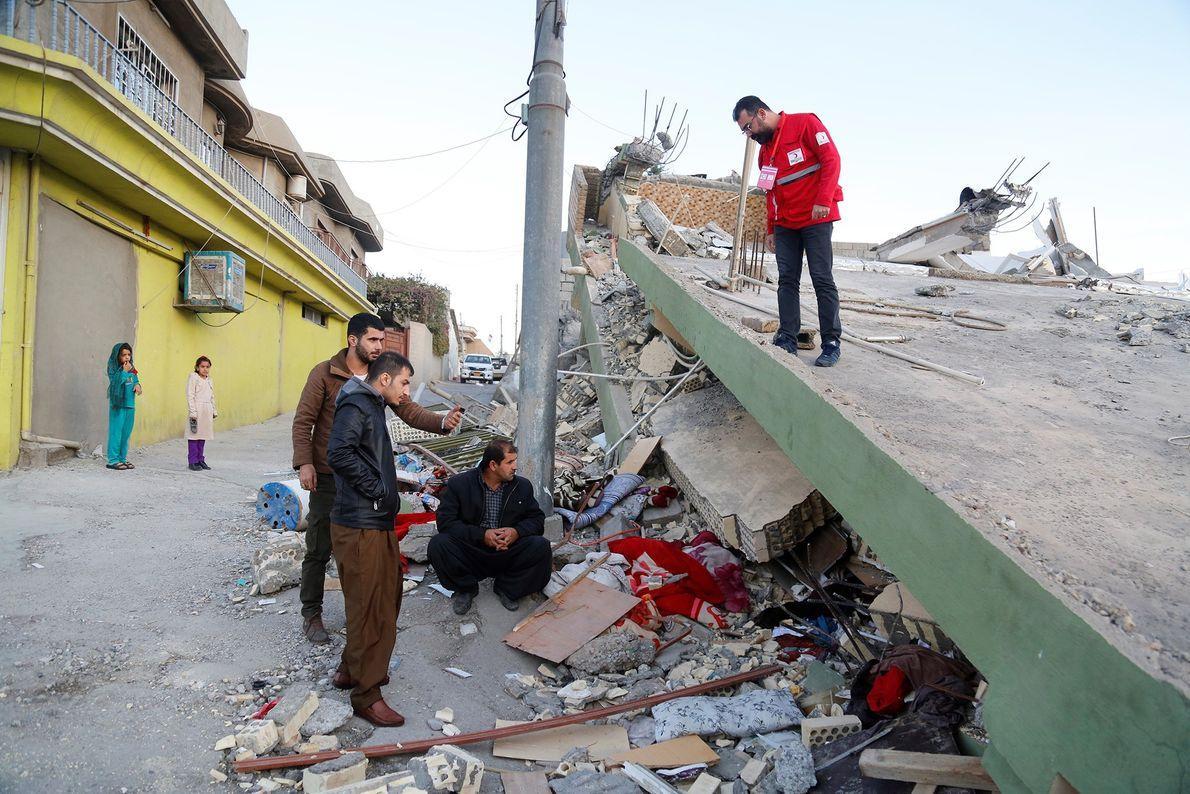Des membres du Croissant rouge turc sont les premiers sur les lieux. Ils observent un bâtiment ...