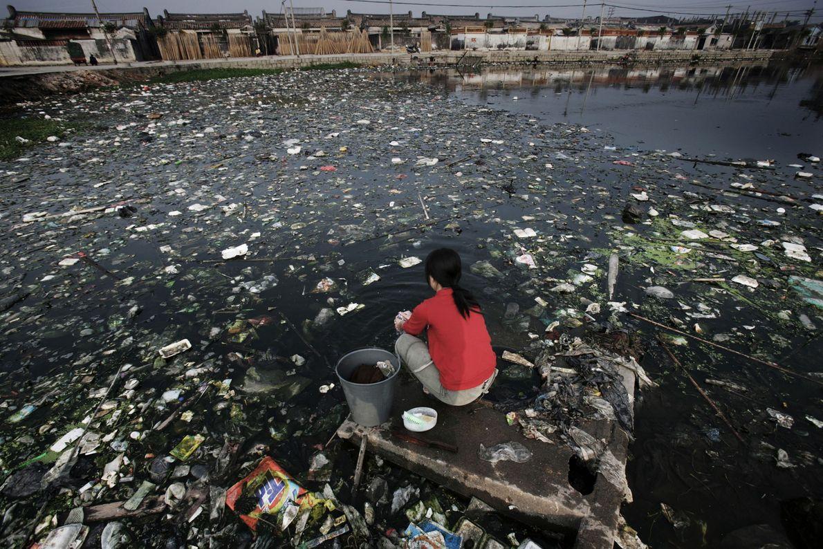 Une femme est assise près d'un des cours d'eau gravement pollués de la province du Guangdong.