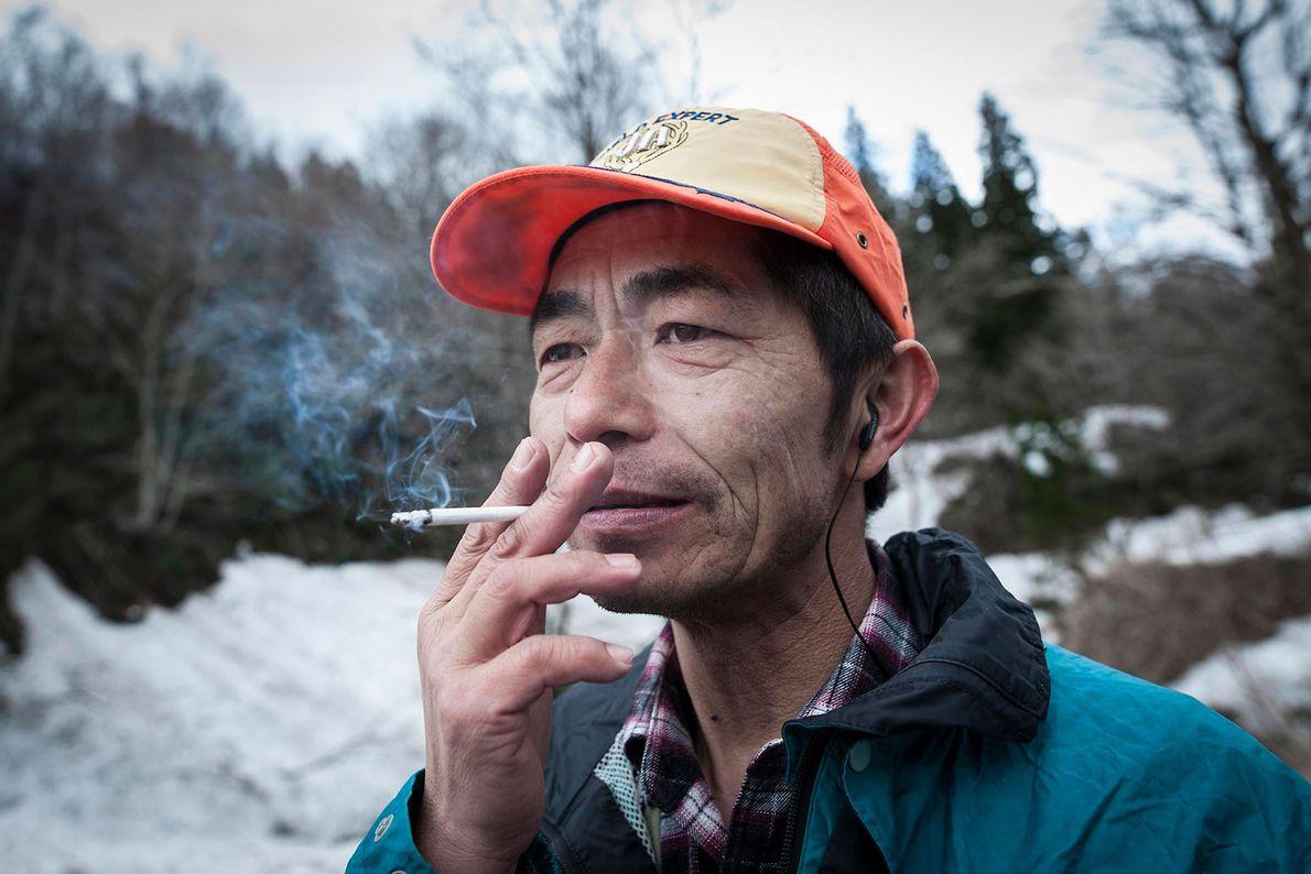 Après une partie de chasse fructueuse, un chasseur matagi fume au pied de la montagne.