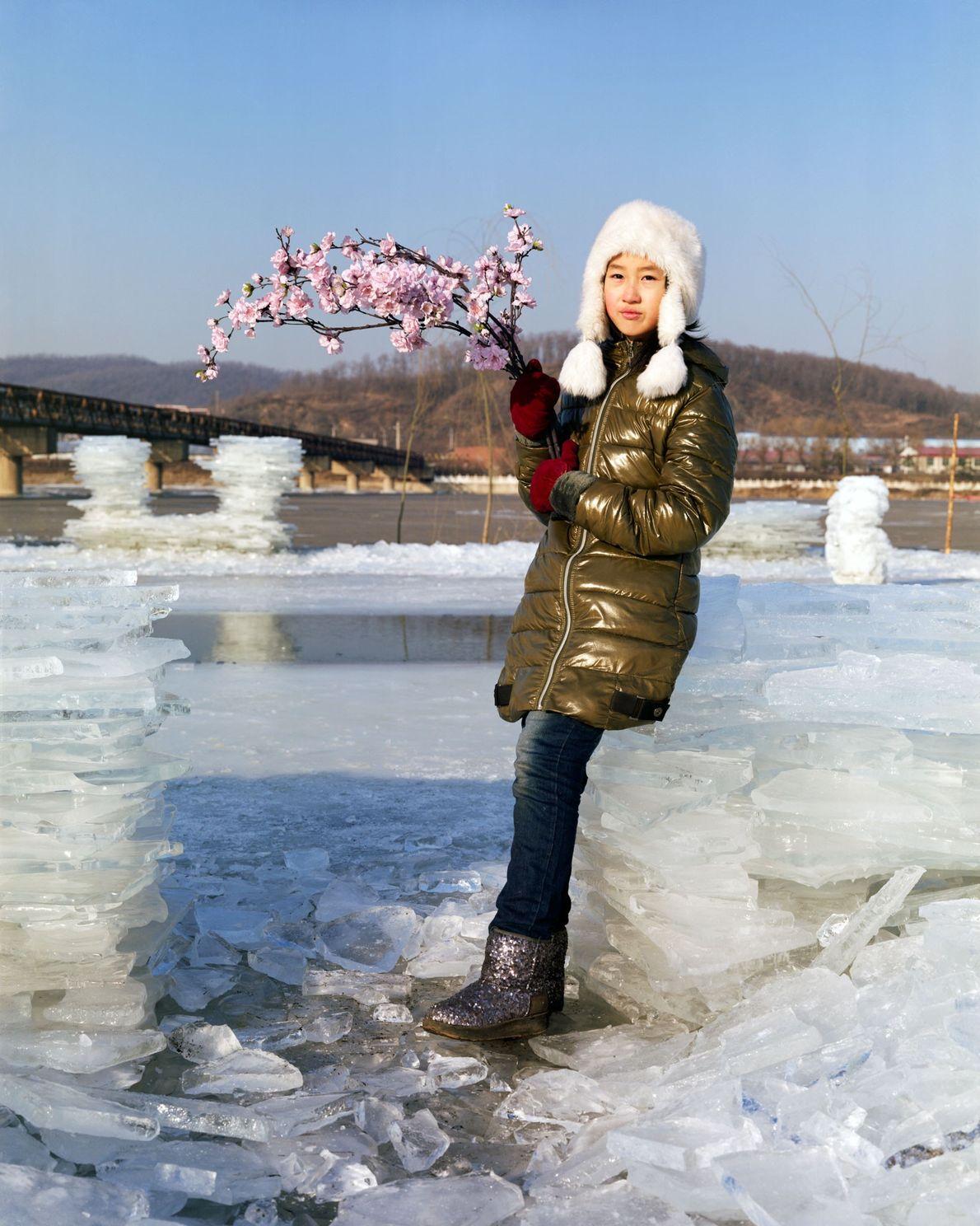 Yuting, 10 ans, pose sur la rive de la rivière Hun avec un bouquet de fleurs ...