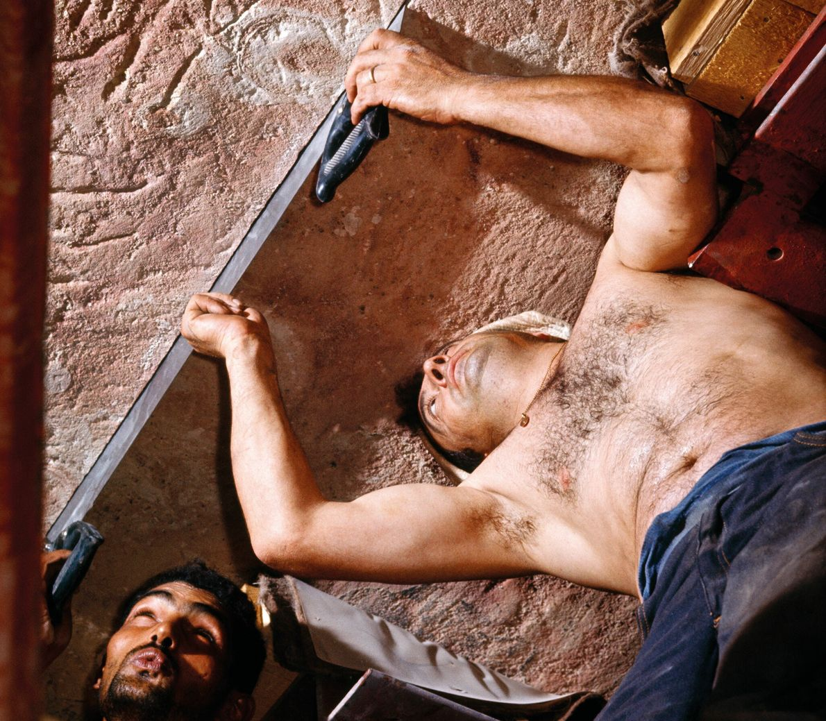 Deux tailleurs de pierre, l'un Italien, l'autre Égyptien, travaillent main dans la main pour faire une ...