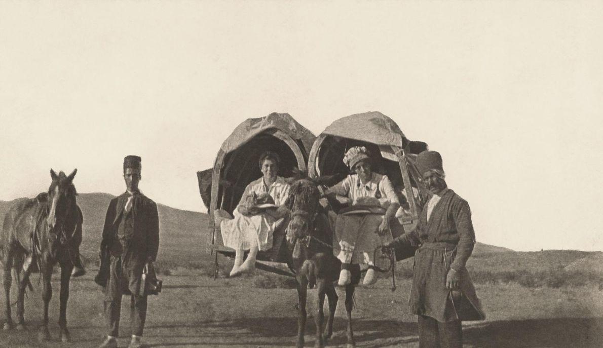 Des hommes se tiennent à côté de deux Américaines qui voyagent en kajeveh, des palanquins en ...
