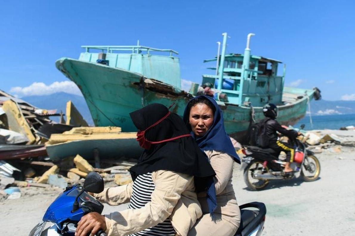 Le 1er octobre, alors que le bilan continue de s'alourdir, des survivants passent en moto devant ...