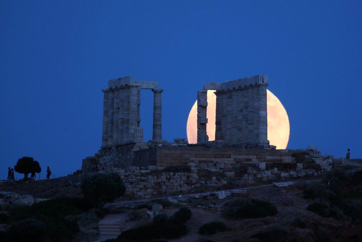 La pleine lune se lève derrière l'ancien temple de Poséidon au cap Sounion, en Grèce, avant ...