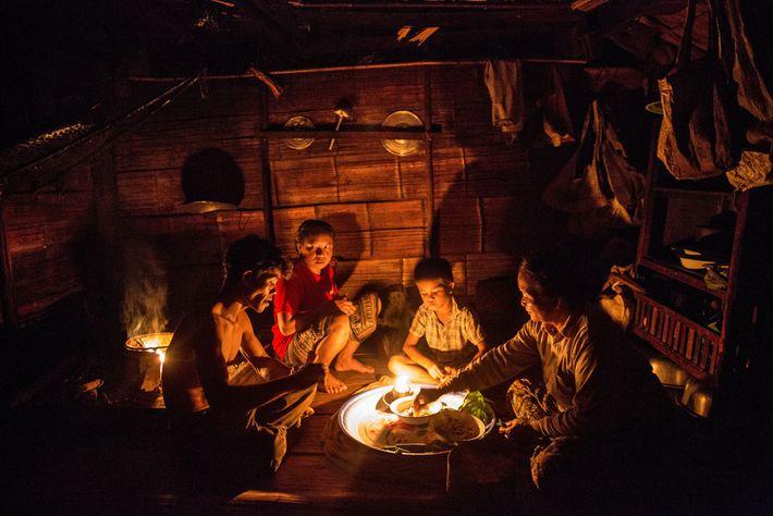 Le long du Mékong, à Ban Khok Yai, trois générations d'une famille dînent à la lueur ...