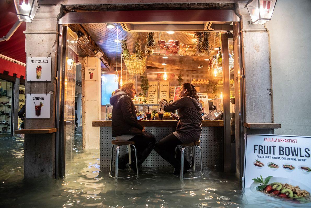 Des locaux s'arrêtent pour prendre un verre malgré les hautes eaux.