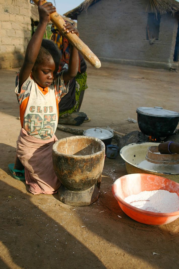 Un enfant pile du manioc - principale denrée alimentaire de base en Afrique Subsaharienne. La photo ...