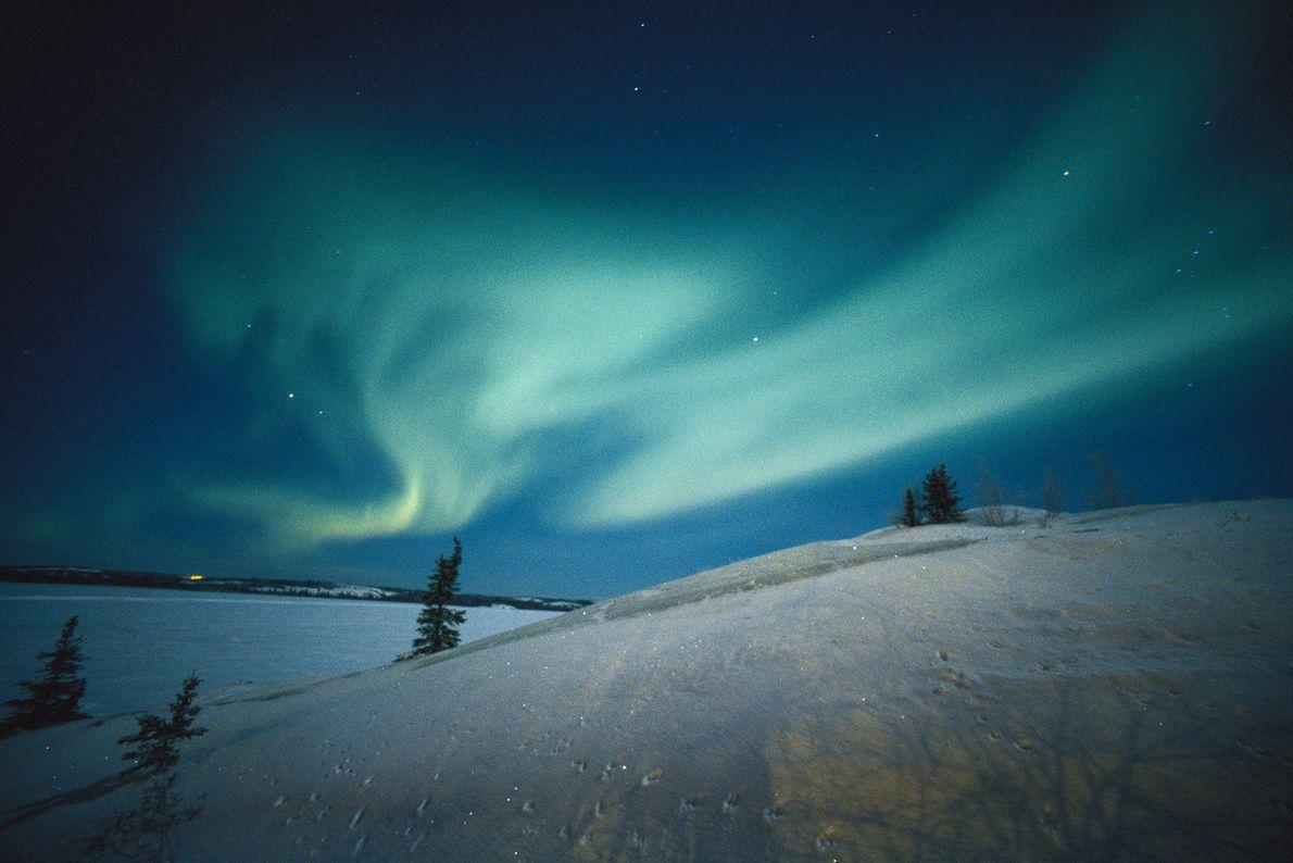 Une aurore traverse le ciel nocturne des territoires du Nord-Ouest du Canada.