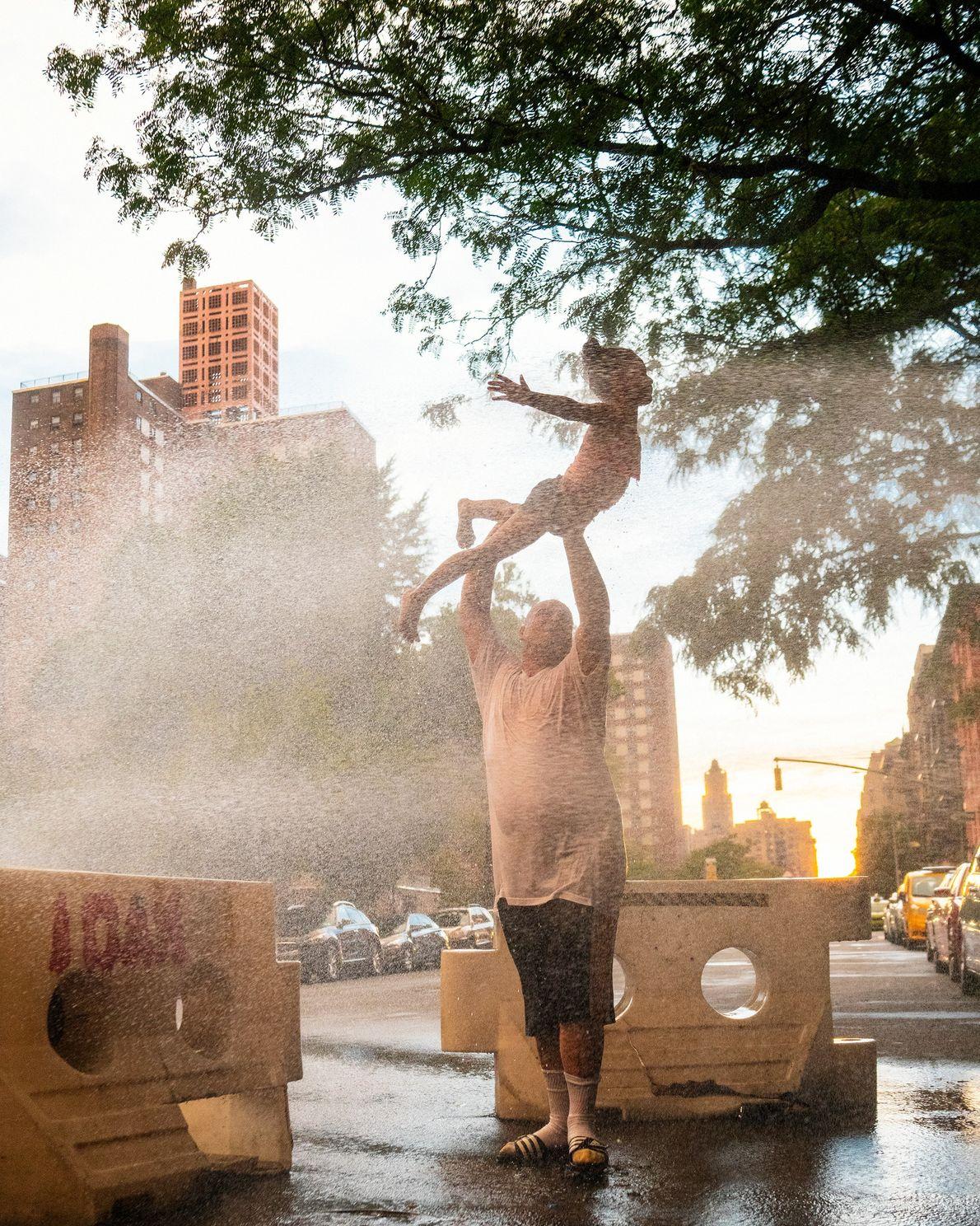 Un père et sa fille profitent d'une bouche d'incendie pour se tenir au frais lors d'une ...