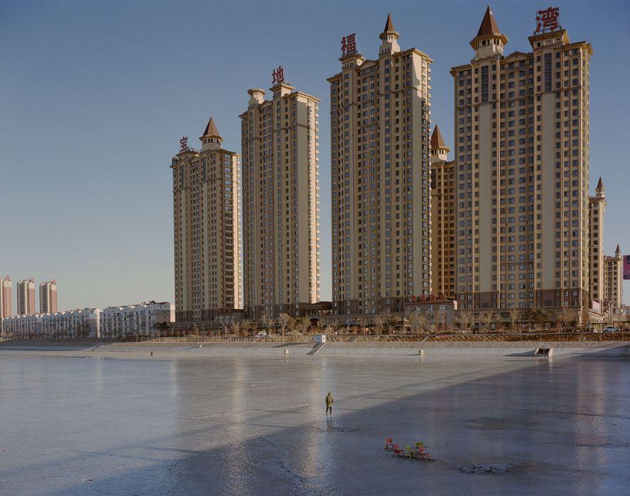 Sur cette photo se dressent des immeubles résidentiels derrière la rivière gelée de Fuxin dans la ...