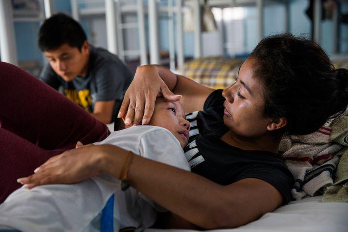 Patricia Flores, qui a quitté le Salvador, console son fils dans un centre d'accueil situé à ...