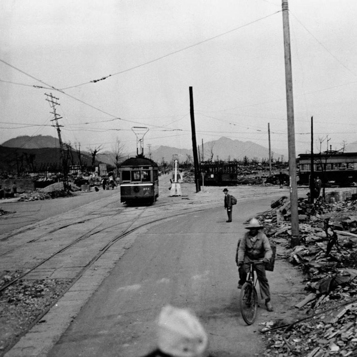Un tramway continue de circuler et quelques civils traversent les ruines d'Hiroshima.