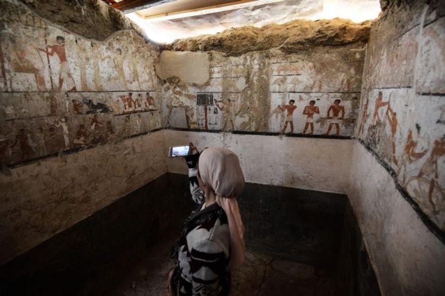 Une femme prend en photo l'intérieur du tombeau d'une prêtresse de l'Égypte Ancienne richement décoré de ...