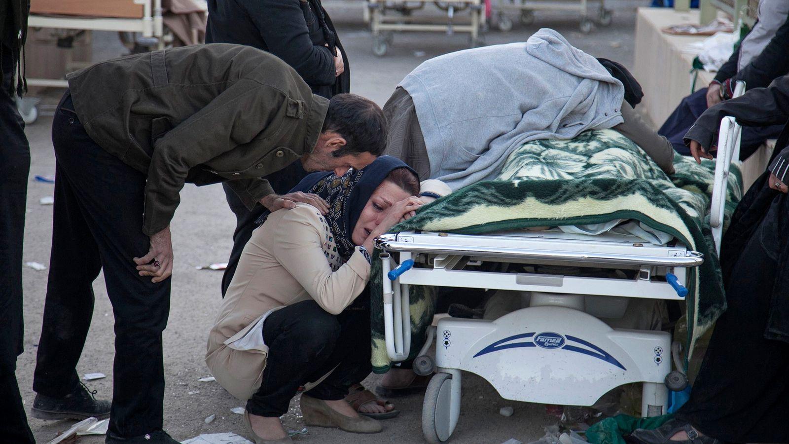 Des proches pleurent une victime du séisme à Sarpol-e-Zahab dans l'ouest de l'Iran.