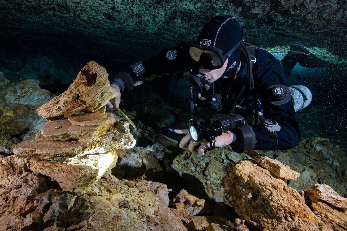 Un plongeur examine des pierres vieilles de 10 000 à 12 000 ans, empilées par d'anciens mineurs qui ...