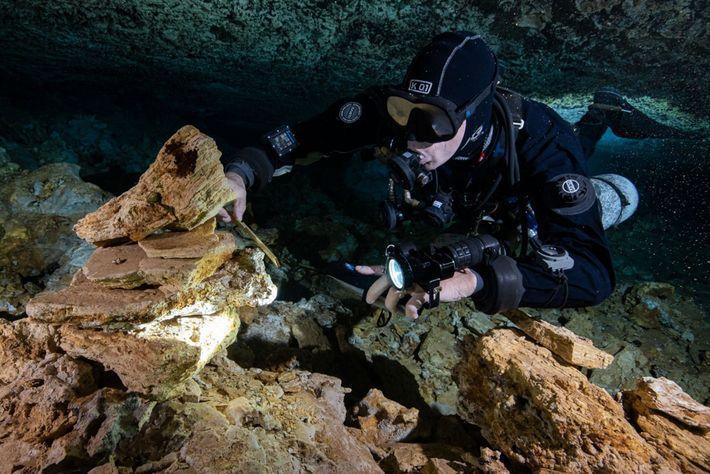 Un plongeur examine des pierres vieilles de 10000 à 12000 ans, empilées par d'anciens mineurs qui ...