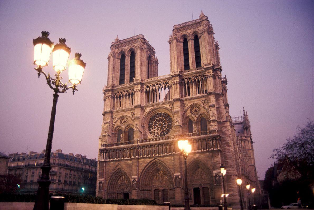 Un réverbère illumine Notre-Dame au crépuscule.
