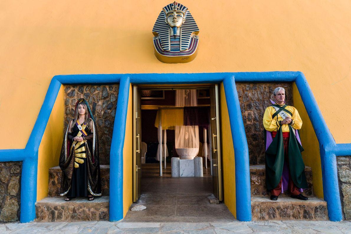 Deux croyants, vêtus respectivement d'un costume de nymphe et de prince maya, gardent l'entrée d'une pyramide ...
