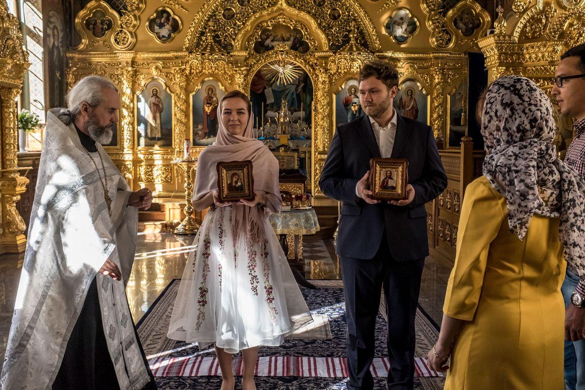 Le prêtre Philip guide Katerina et Yevgeny Bolonnikov au cours de la cérémonie de leur mariage. ...