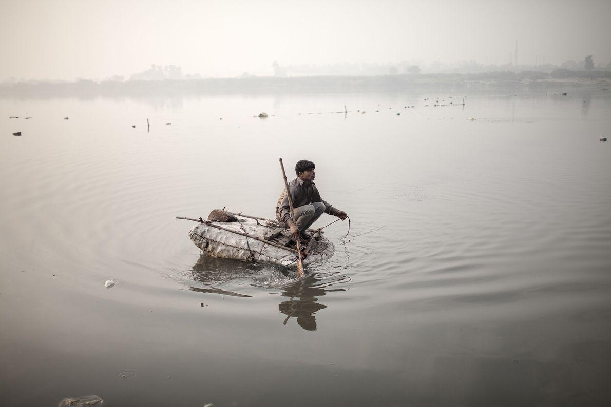 Un garçon sans abri pêche des pièces de monnaie en utilisant une ficelle et un aimant ...