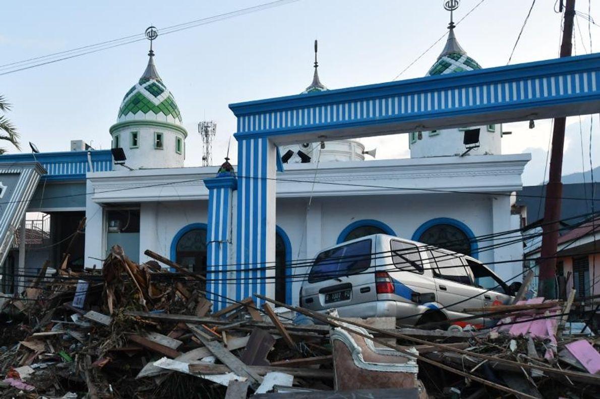 À Palu, des décombres et une voiture hors d'état de marche s'entassent devant une mosquée après ...
