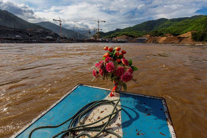 Un bateau décoré d'un bouquet de fleurs artificielles se dirige vers le site du barrage de ...