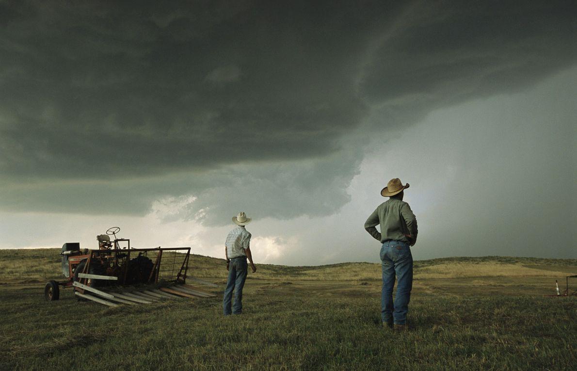 Des fermiers observent la formation de nuages lourds au-dessus des dunes de sable d'Ogallala, au Nebraska, ...