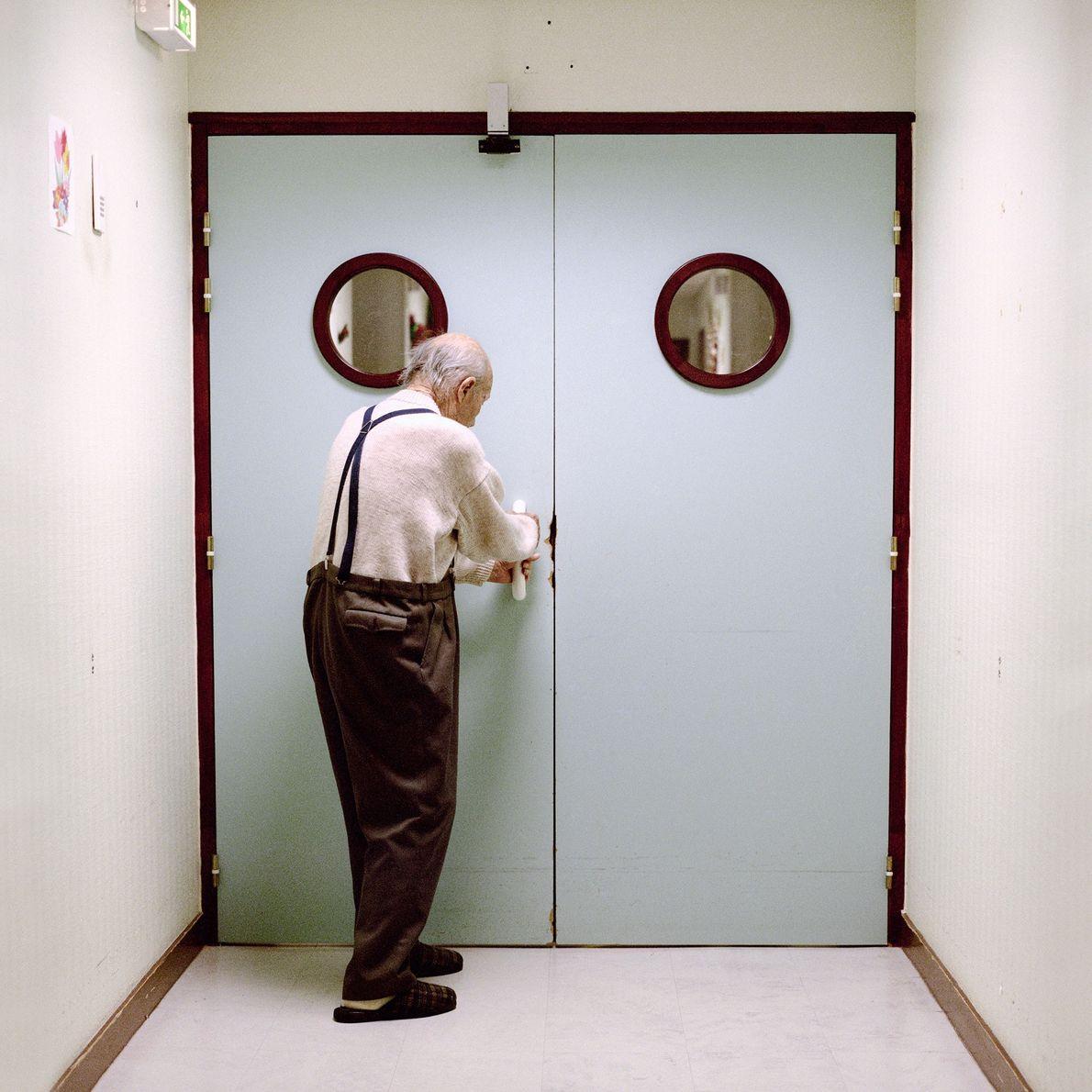 Un résident se tient devant la porte verrouillée menant à la sortie du département.