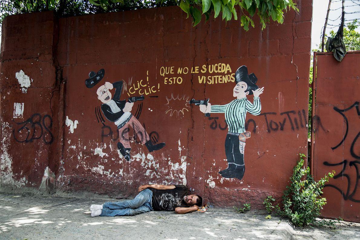 Un homme dort dans la rue sous une oeuvre représentant un échange de tirs. Pendant plus ...