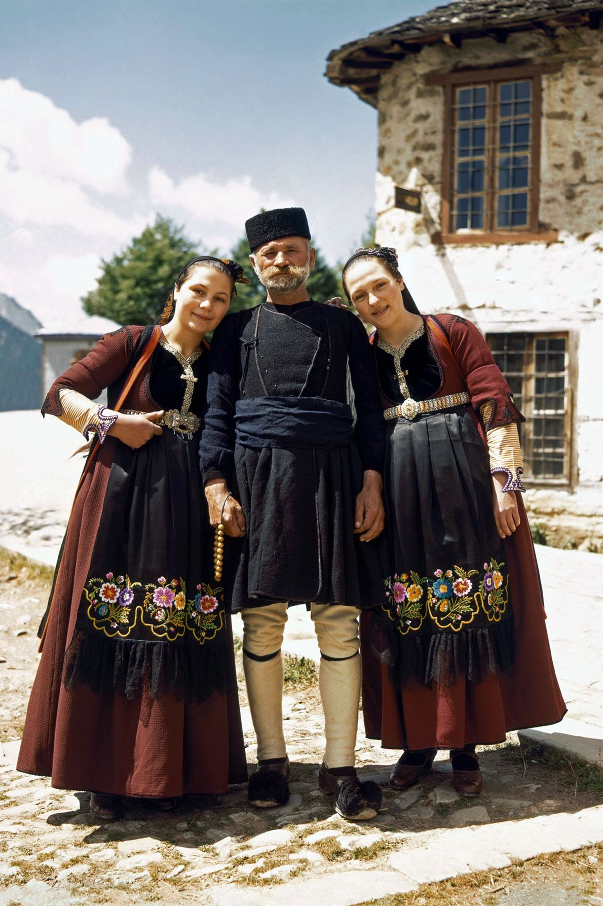 Vêtues de leur tenue traditionnelle, ces deux filles posent aux côtés de leur père, un berger, ...