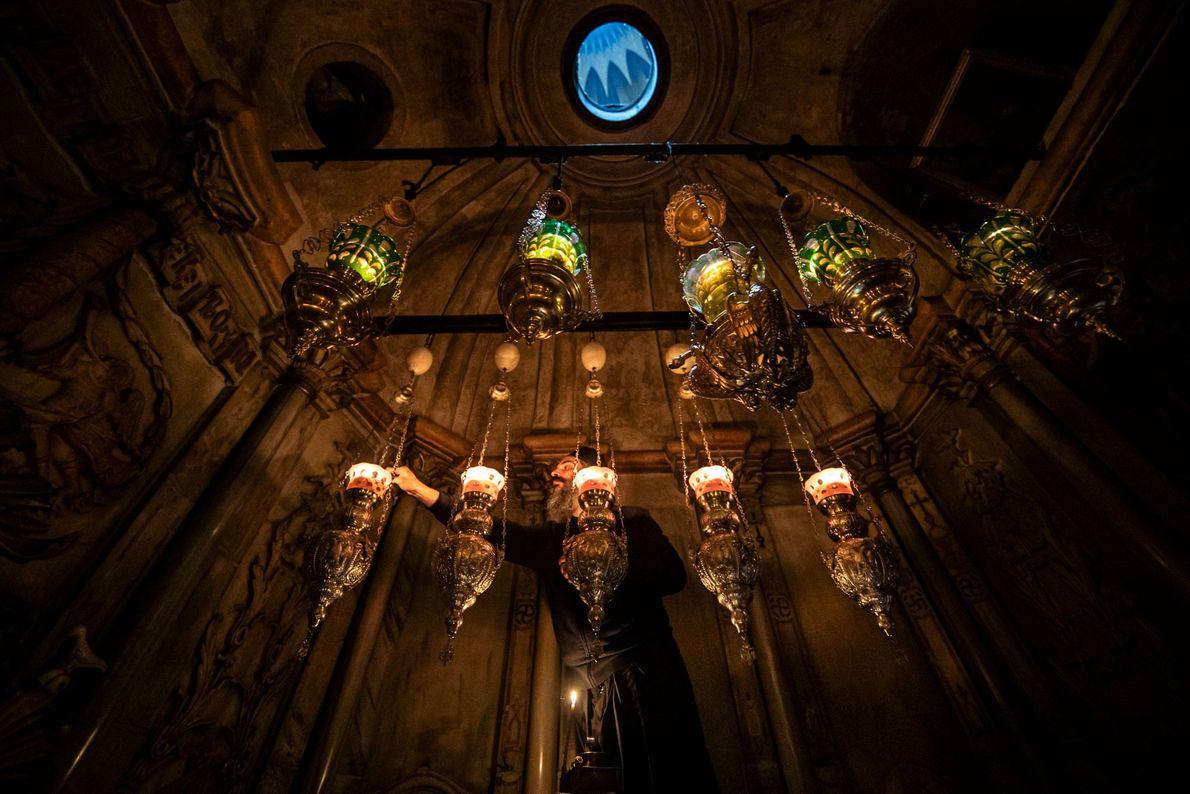 Le Père Vasilios de l'Église grecque orthodoxe allume des lampes à l'intérieur de l'Édicule pendant la ...
