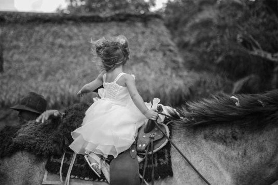 Une fillette se tient sur un cheval pour aller à son baptême.