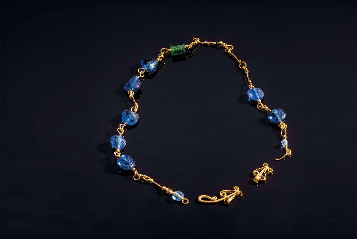 Un collier en or composé de perles de verre ornait le cou d'une femme ensevelie dans ...