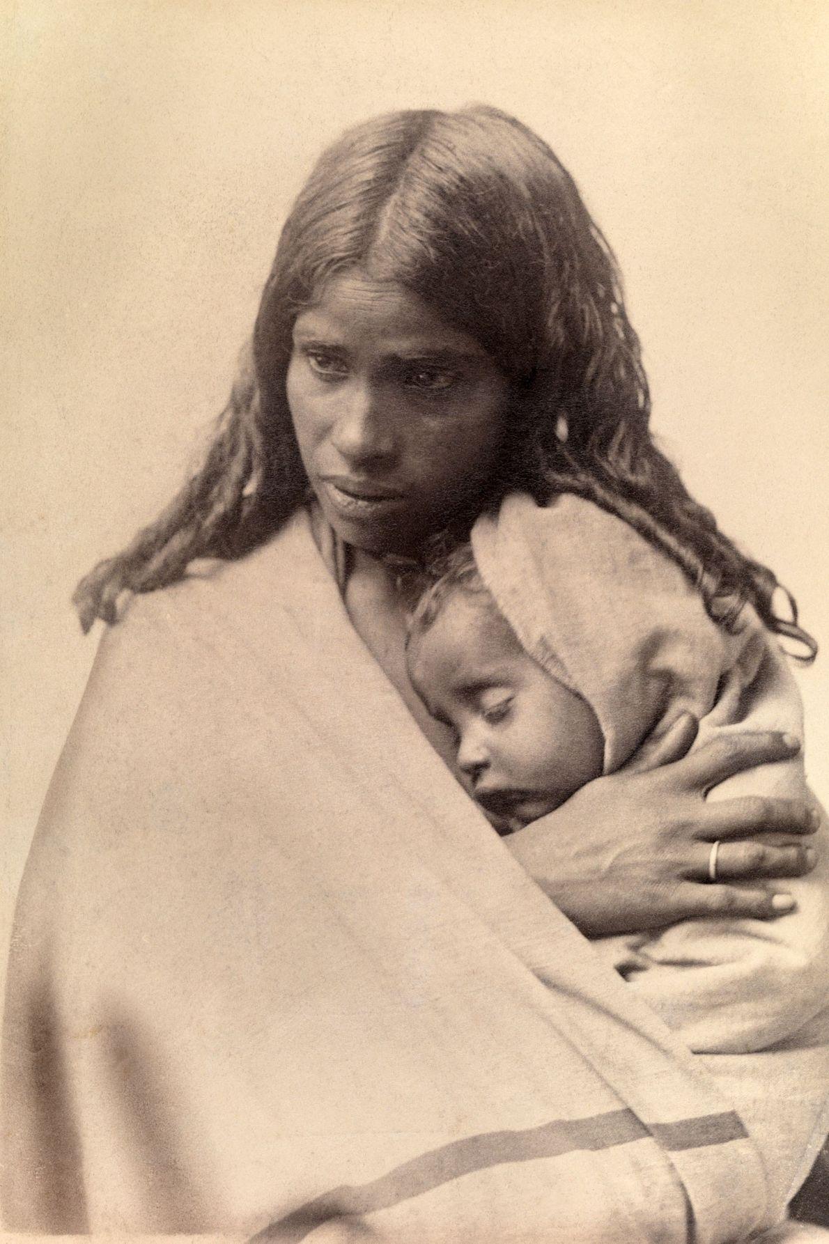 Un bébé Toda dort dans l'étreinte de sa mère à Nilgiri Hill, près de Madras, en ...