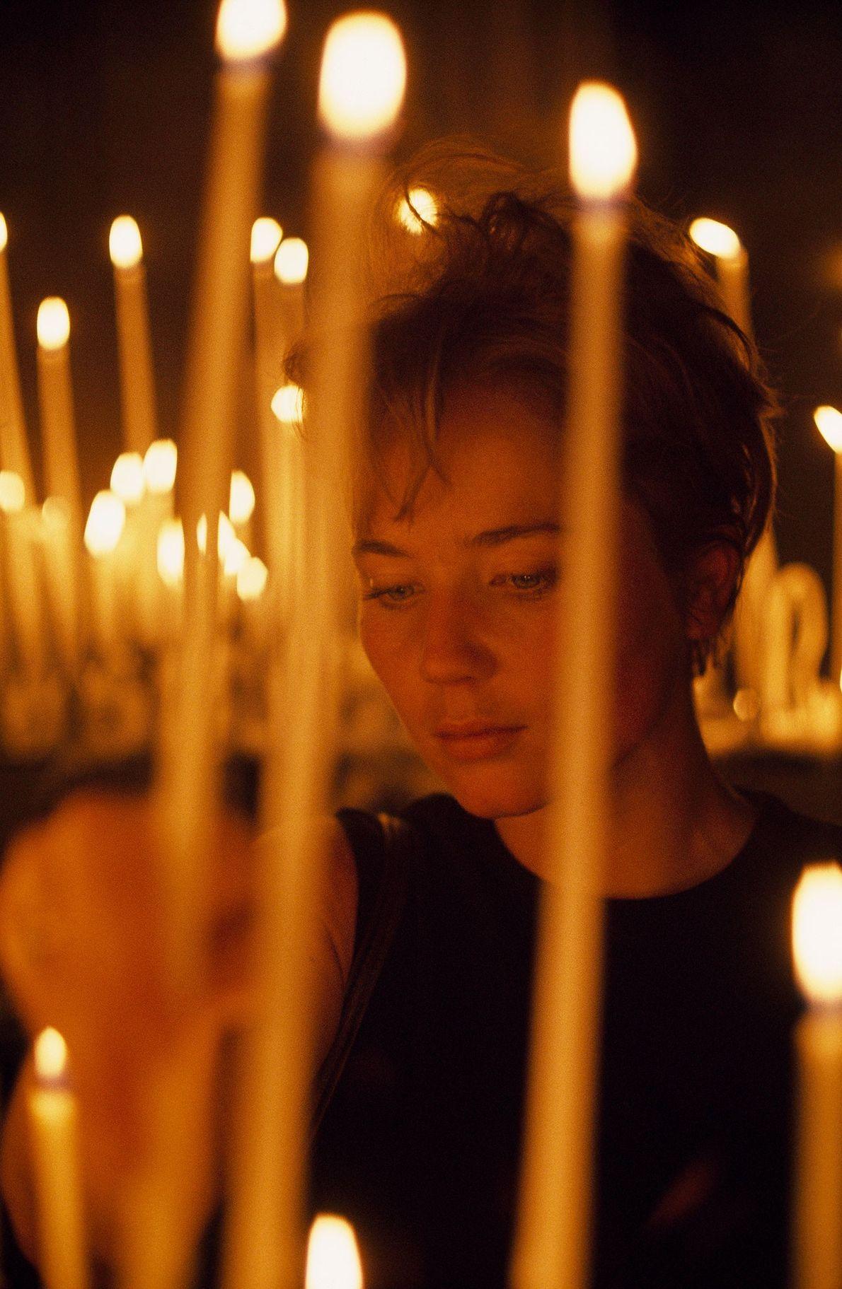 Une touriste américaine allume une bougie dans la cathédrale en 1968.