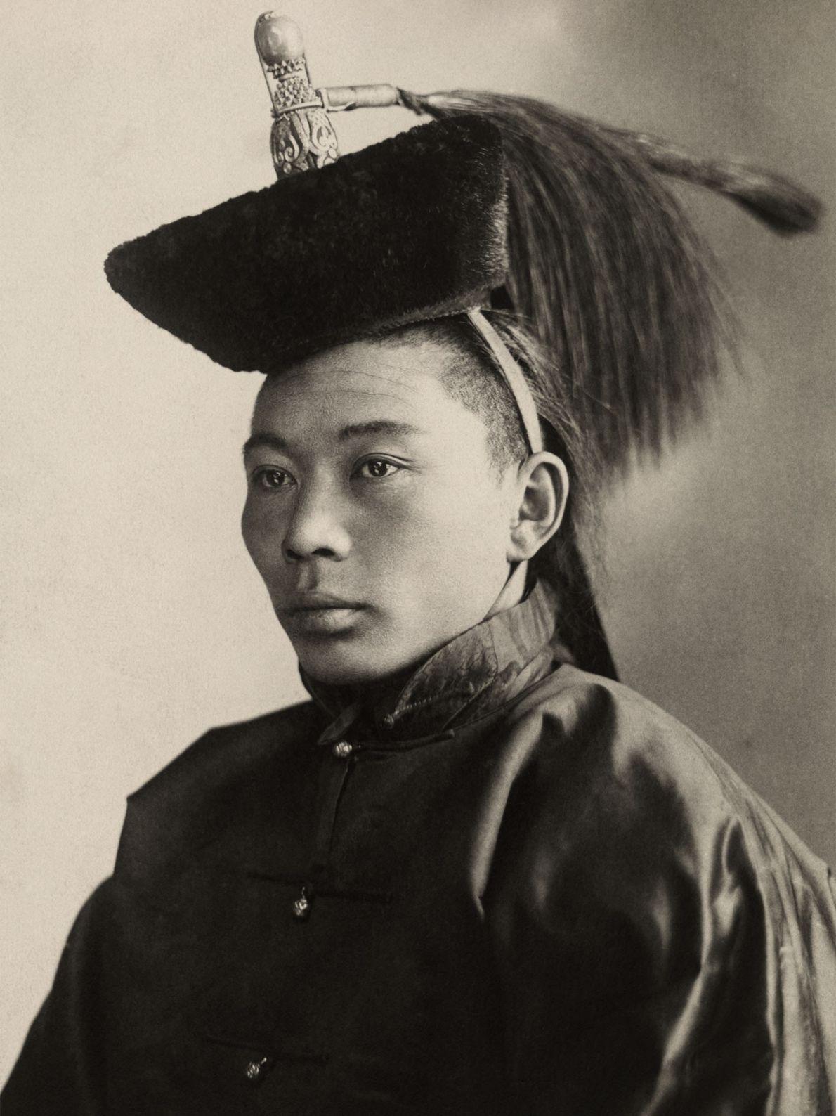 Un jeune prince mongole prend la pose pour une photo avec une coiffe ornée qui indique ...