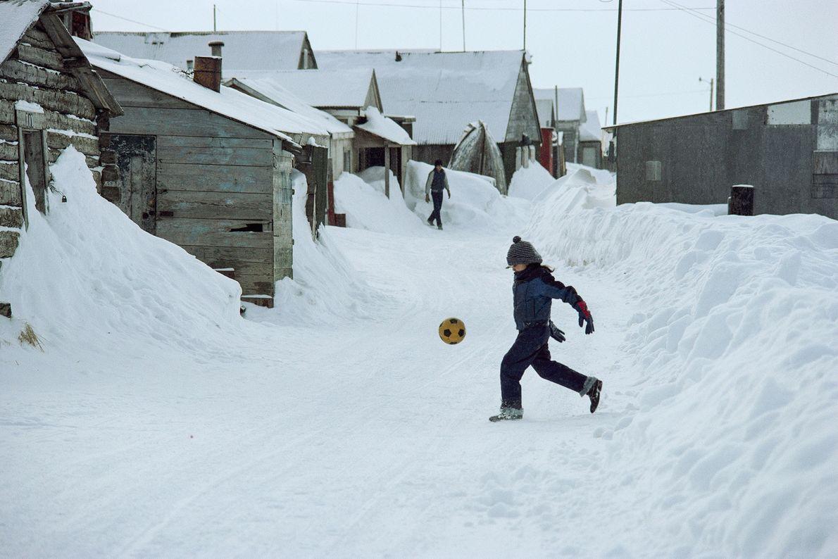 Un jeune garçon joue au football dans les rues enneigées de Barrow, en Alaska.