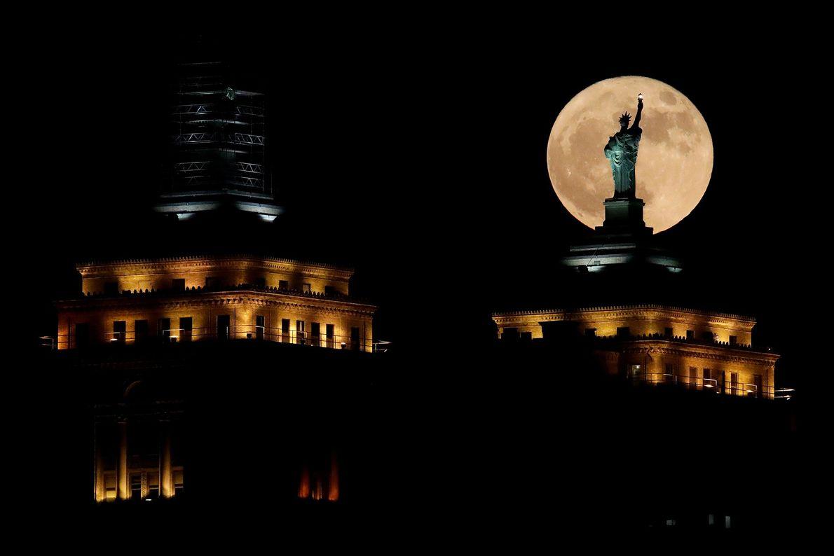 La Super Lune s'élève dans le ciel derrière une réplique de la statue de la Liberté ...