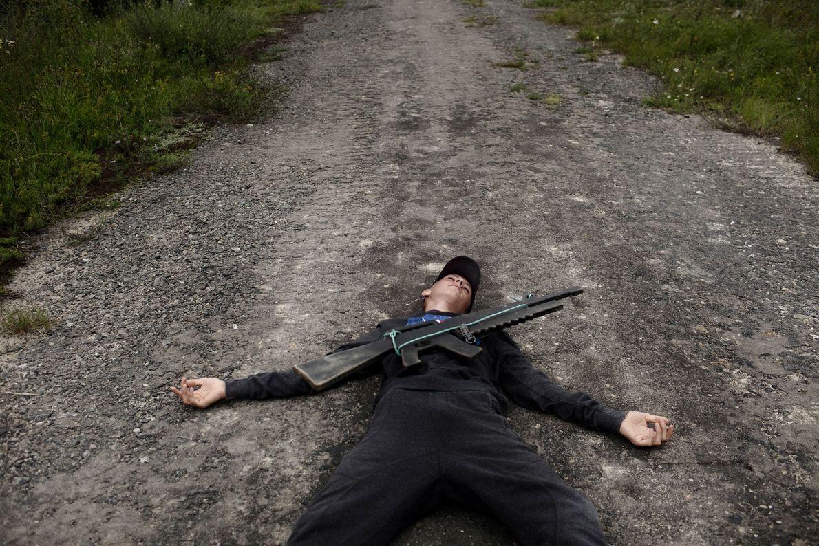 Un jeune Ukrainien allongé sur le sol pour prétendre avoir été abattu par le « feu ...