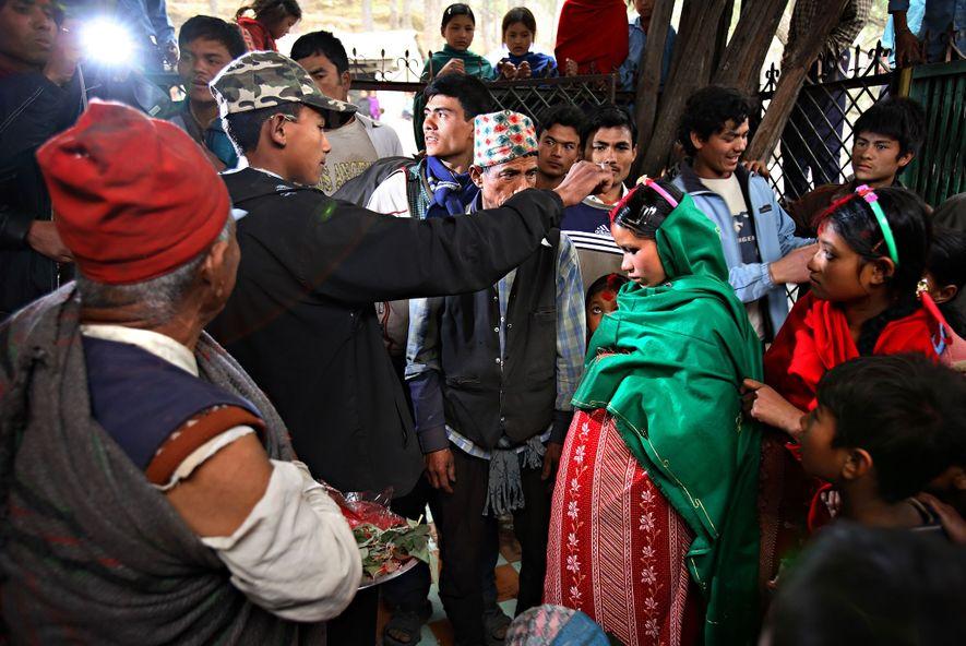 Durga Bahadur Balami, 17 ans, peint de rouge le front de Niruta Bahadur Balami, 14 ans et enceinte de neuf mois, alors qu'ils deviennent officiellement mari et femme dans le village de Kagati, au Népal, le 23 janvier 2007. Niruta a emménagé avec la famille de Durga et est tombée enceinte alors qu'ils n'étaient que fiancés. Dans certains cercles du peuple newar, plus tolérant, cela est permissible.