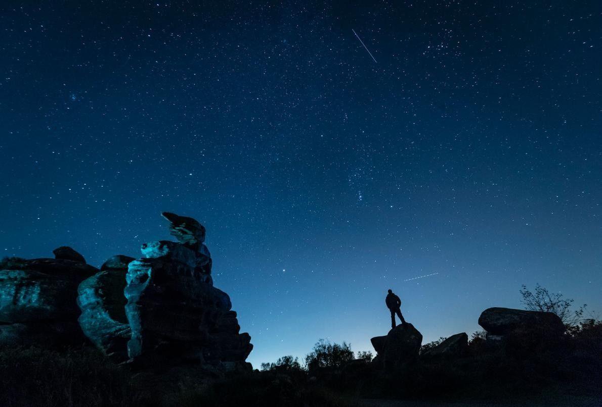 Un avion et un satellite passent sous les étoiles à Brimham Rocks, dans le Yorkshire, au ...