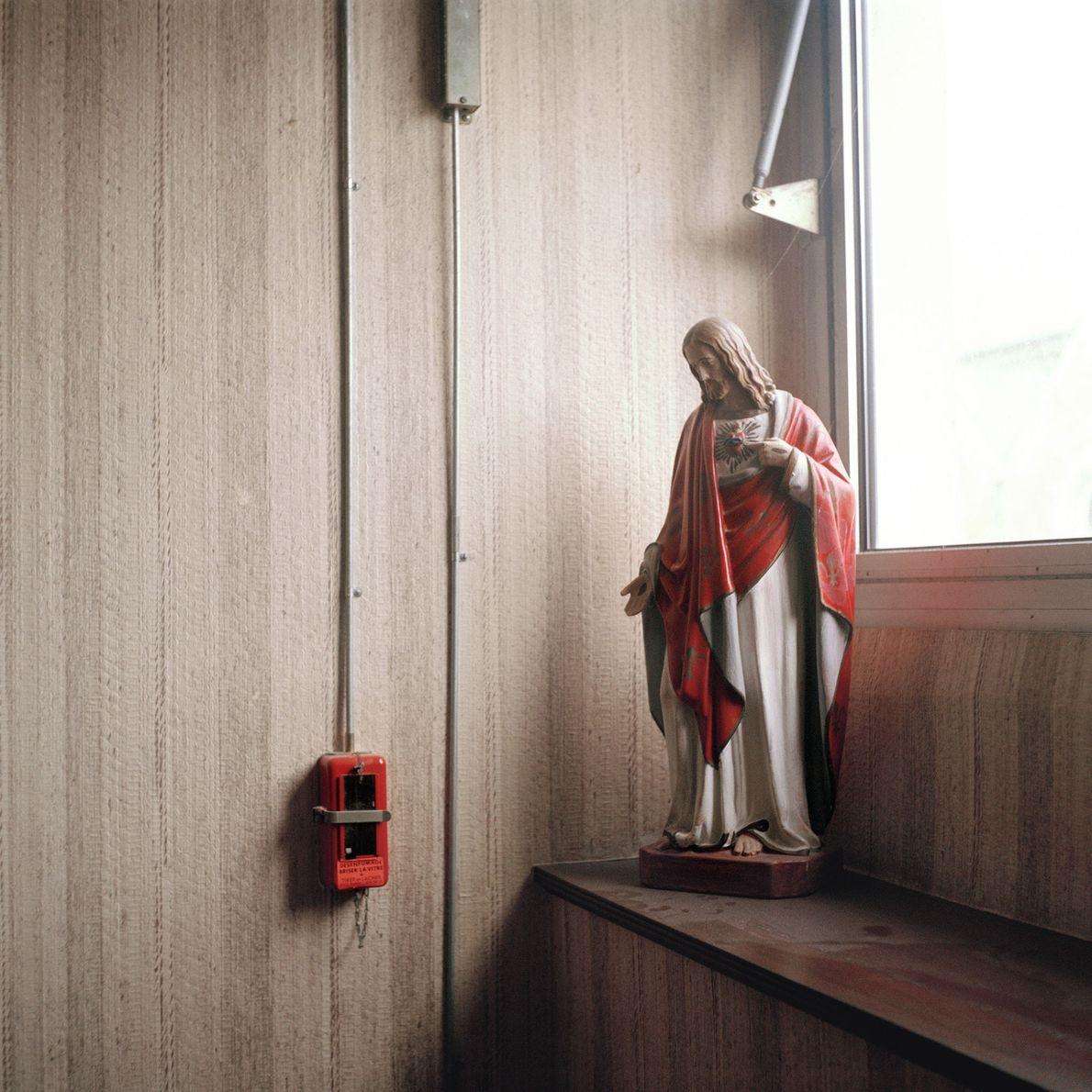 Une statuette de Jésus posée près d'une fenêtre dans la cage d'escalier du département.