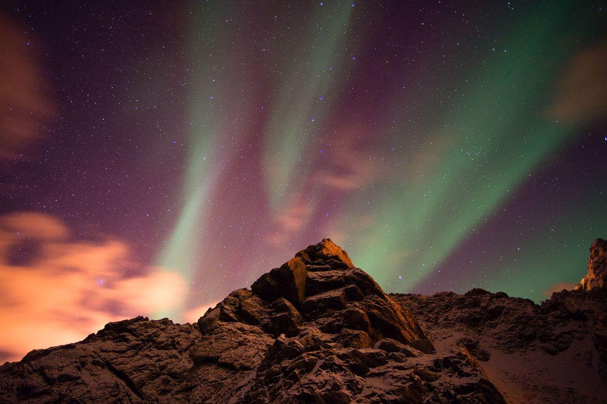 Une lueur boréale colore le ciel de rose dans le chapelet d'îles Vesterålen, en Norvège.