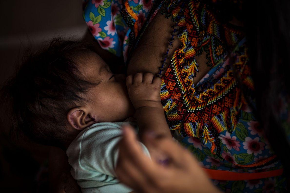 Une jeune mère donne le sein à son petit.