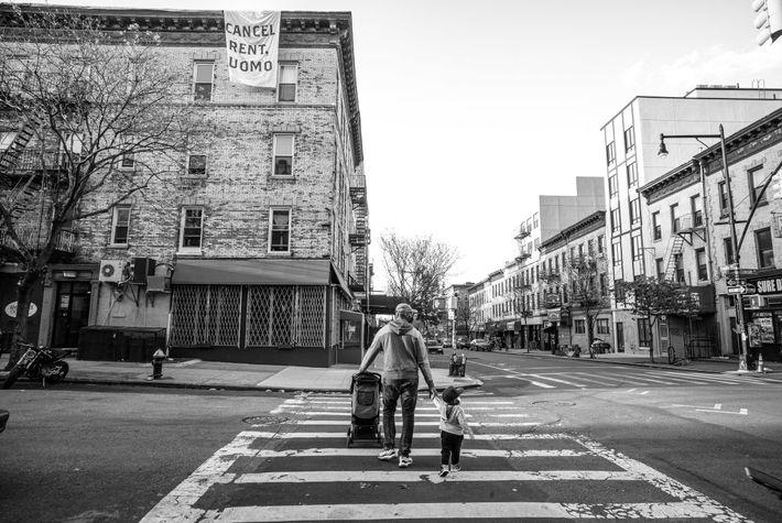 Un père et son fils traversent Nostrand Avenue à Brooklyn. Au-dessus d'eux, une bannière appelle le ...