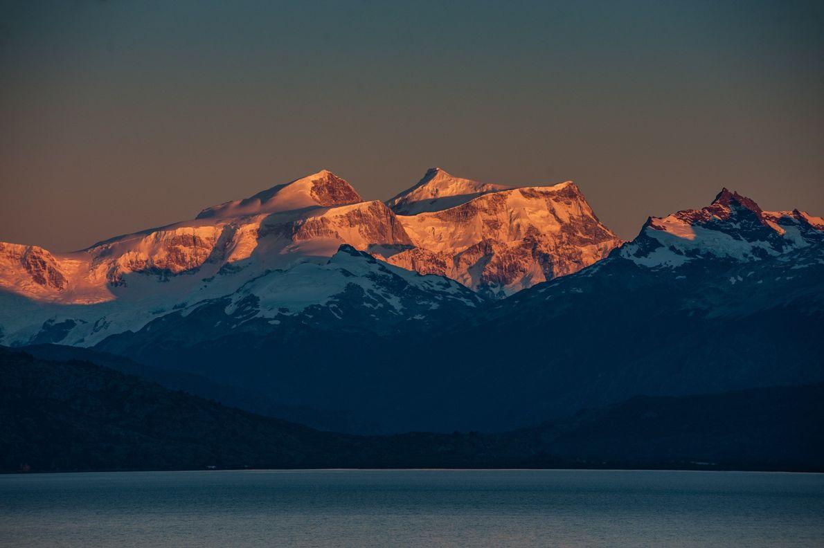 Montagnes et glaciers s'illuminent au coucher de soleil derrière les eaux paisibles du lac General Carrera.
