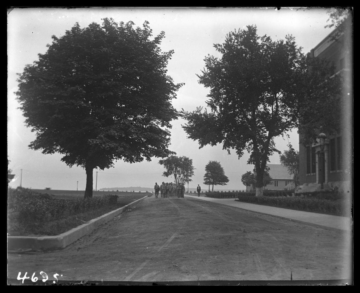 Un gardien de la maison de correction marche aux côtés d'un groupe de garçons en 1913.