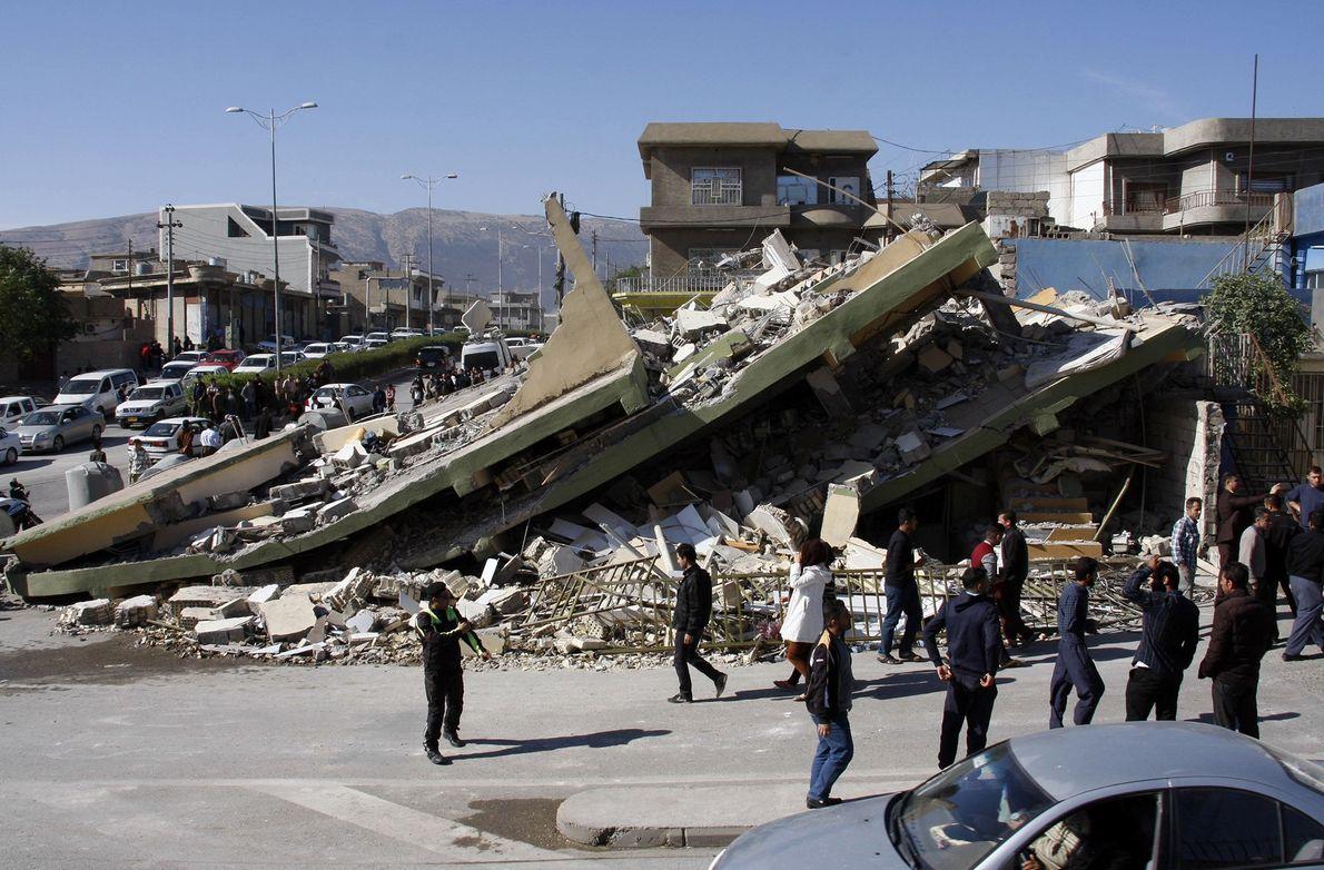 Des habitants se rassemblent autour d'un bâtiment dans la ville montagneuse de Darbandikhan dans le Kurdistan ...